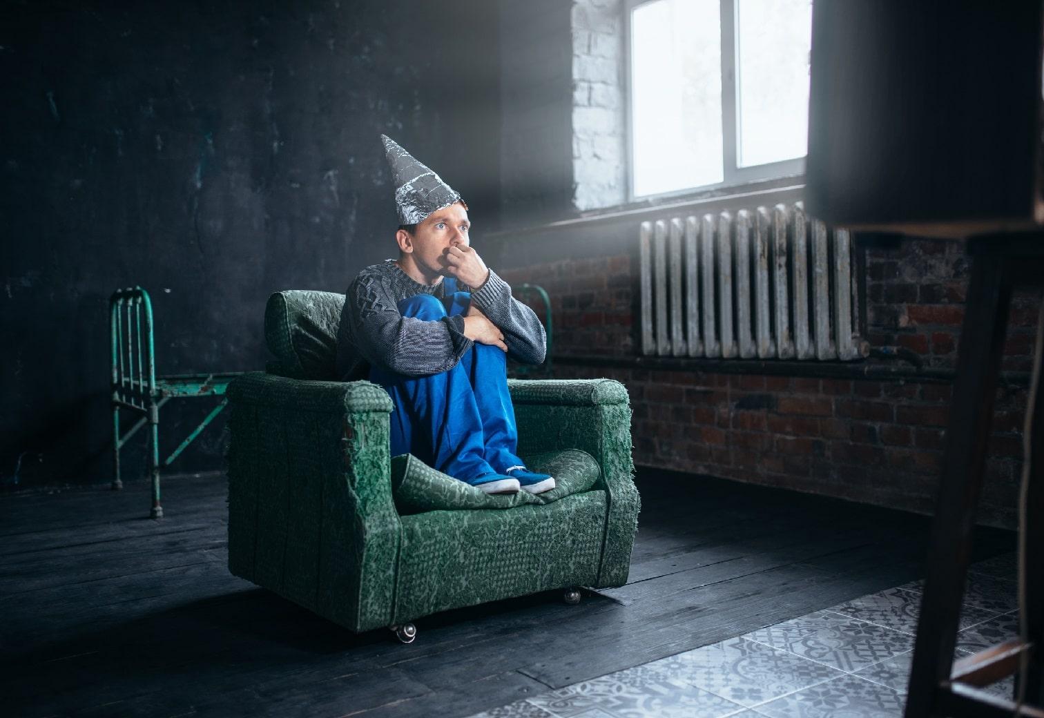 Fobibehandling.dk Alle er bange for noget. Her sider en ung mand i en lænestol i en mørk kælder med en sølvpapir hat på hovet, Måske har han phobofobi